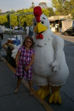 Nadia with a large mascot in front of one of Pollo Feliz restaurants on Guadelupe in San Miguel de Allende, Mexico.