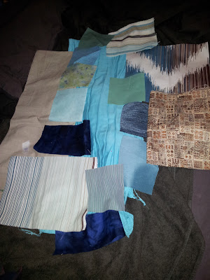 Selection of brown/blue/green fabrics laid out with slightly bad lighting