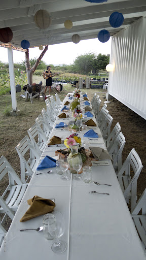 A table for twenty is set with rustic arrangements of produce under the roof of a barn at ARTfarm.