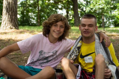 A Camp Barnabas Participant poses with his counselor in the woods after a fun day of swimming.