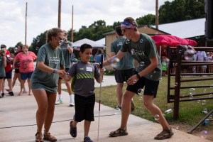 A Young Boy Is Welcomed By Camp Counselors As He Arrives At Camp Barnabas.