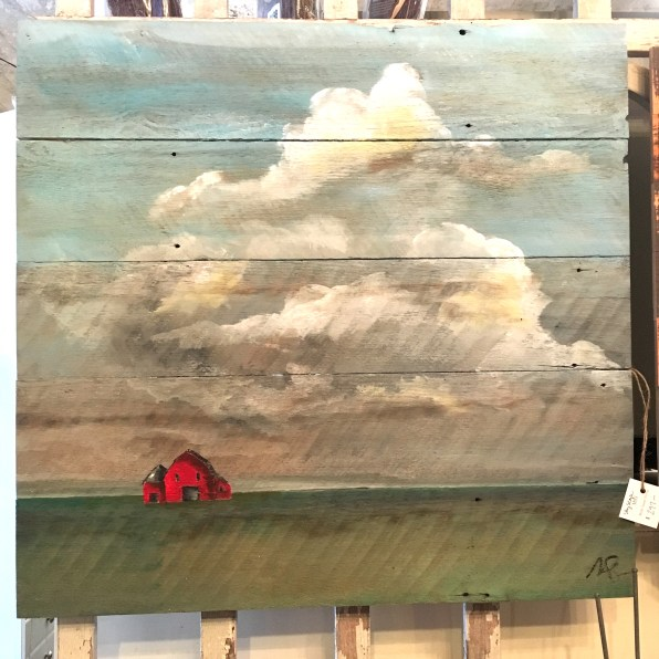 a painting on wood board featuring a small red barn in a vast country landscape