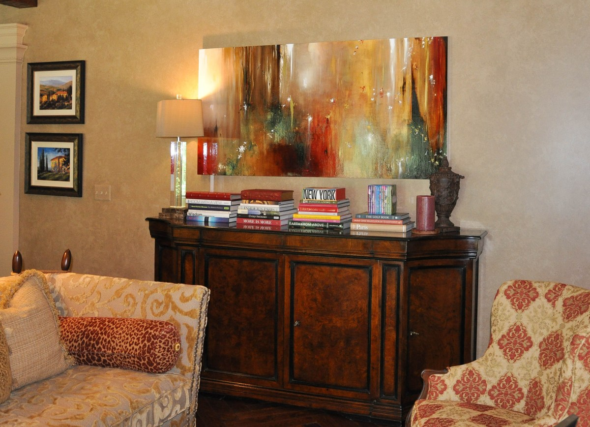 An abstract mixed media painting on panel by artist Jennifer JL Jones hangs in a family room over a buffet and features rich earthy tones of red, caramel, moss, and deep brown.