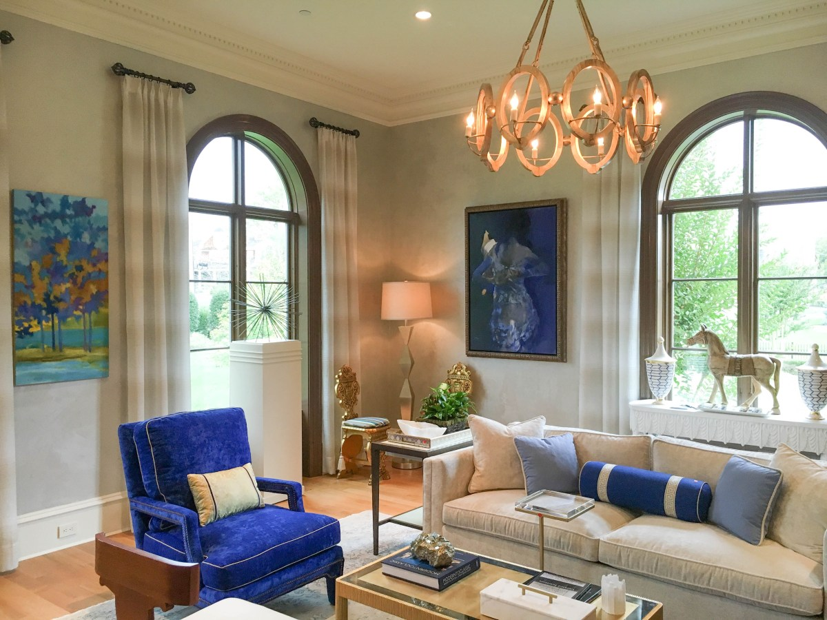 This sophisticated living room by Lorna Gross Interior Design showcases neutral decor in shades of off-white that is punctuated by pops of bright blues.