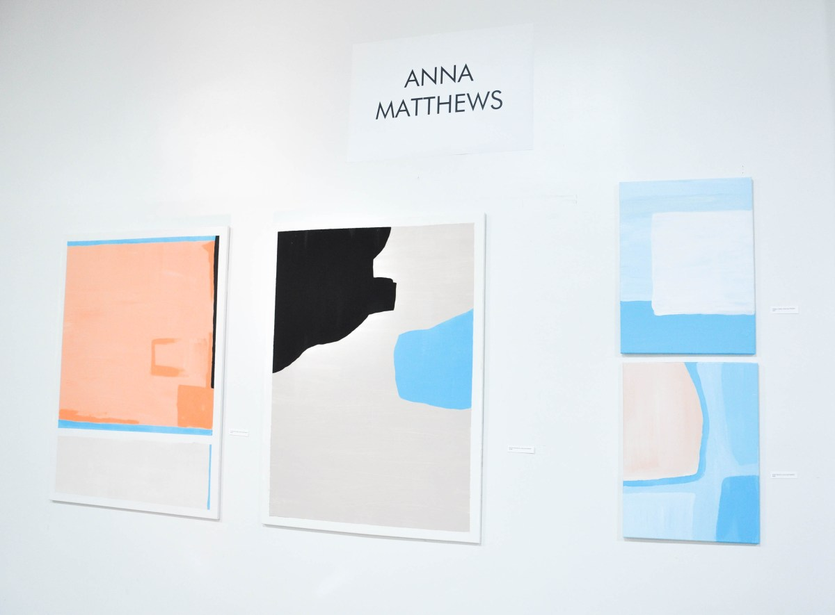 An installation view from a gallery opening of four abstract paintings by Anna Matthews