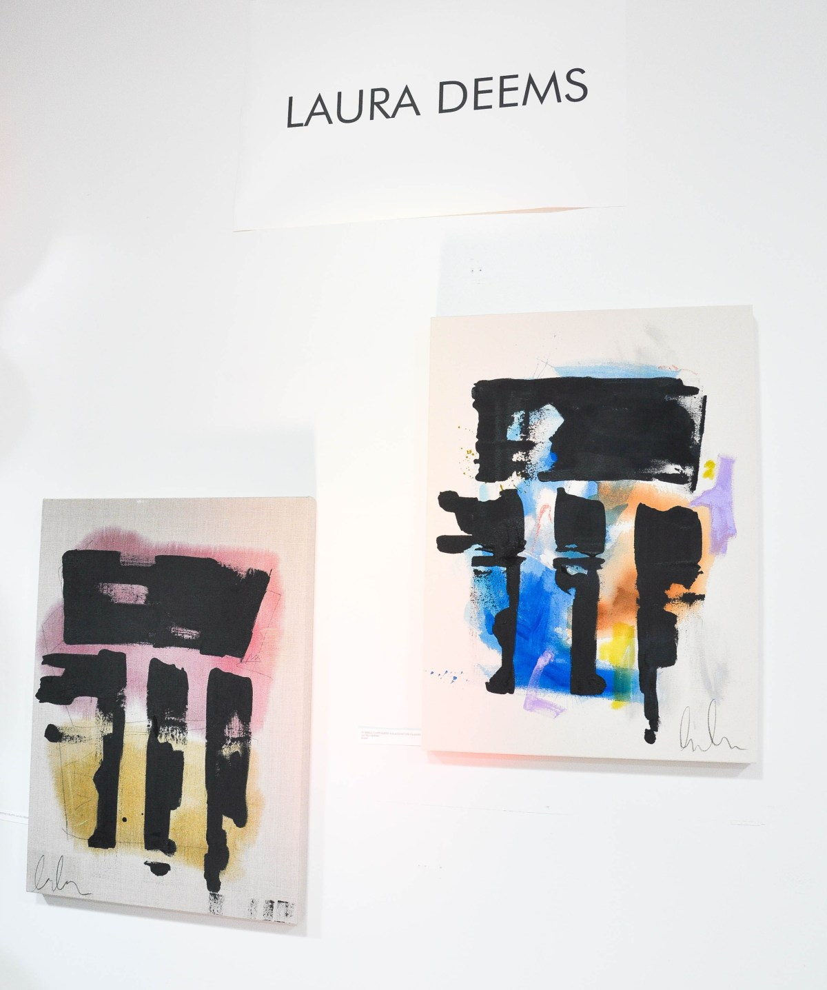 Two small abstract paintings by Laura Deems hang on white walls at a gallery exhibition.