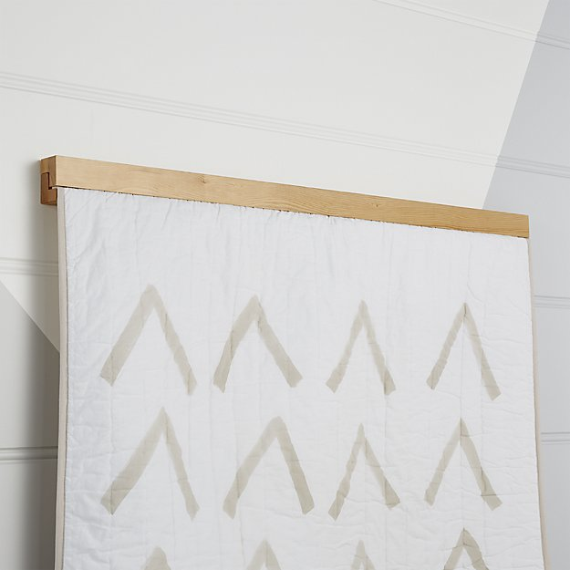 Contemporary and sleek wall hanger, offered in a light, natural wood tone, is the perfect size for displaying a baby quilt as wall art.