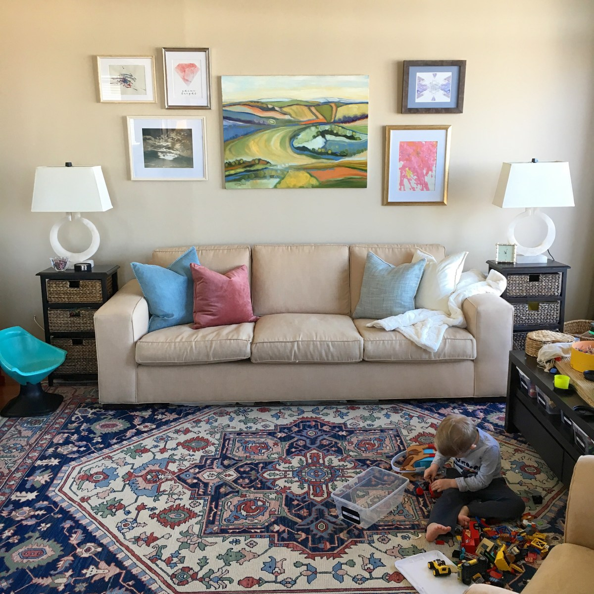 A gallery wall over a family room couch designed with lighter and brighter colors for the summer months