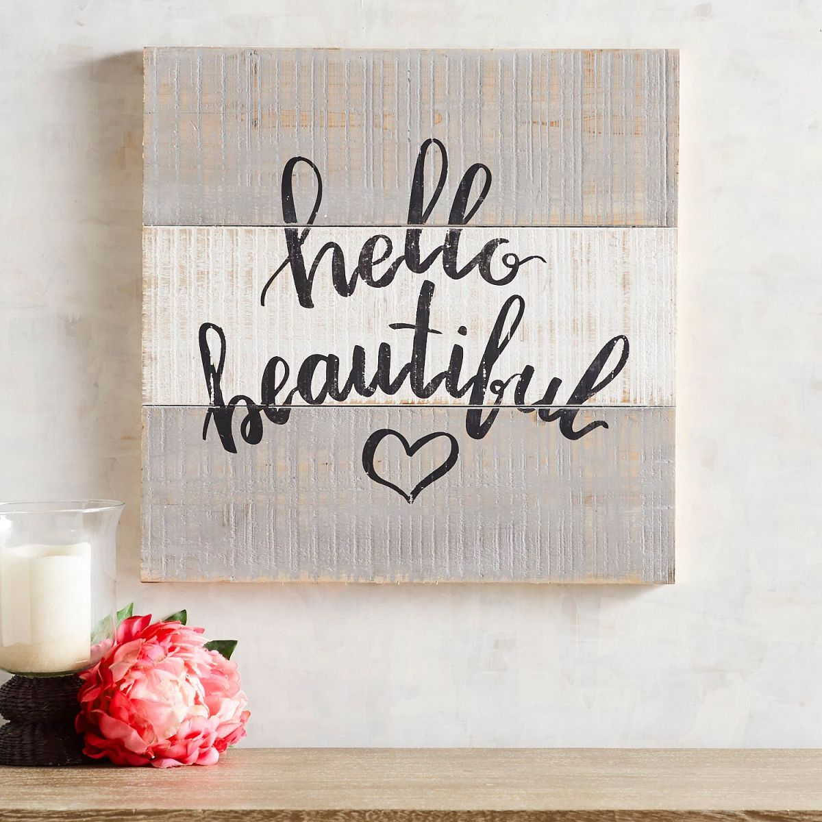 Rustic planked gray and white wall art from Pier One that reads Hello Beautiful in black script font with a small heart below