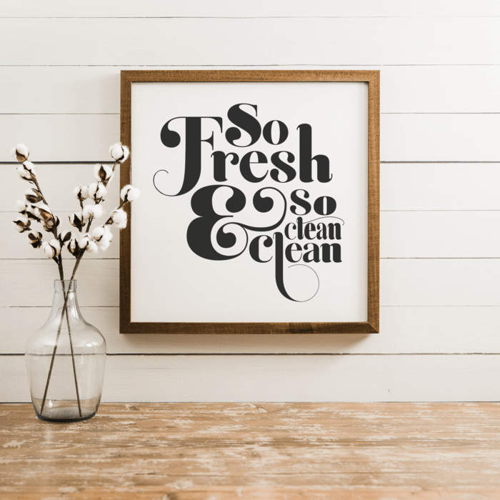 A framed white print with black lettering that reads So Fresh & So Clean Clean