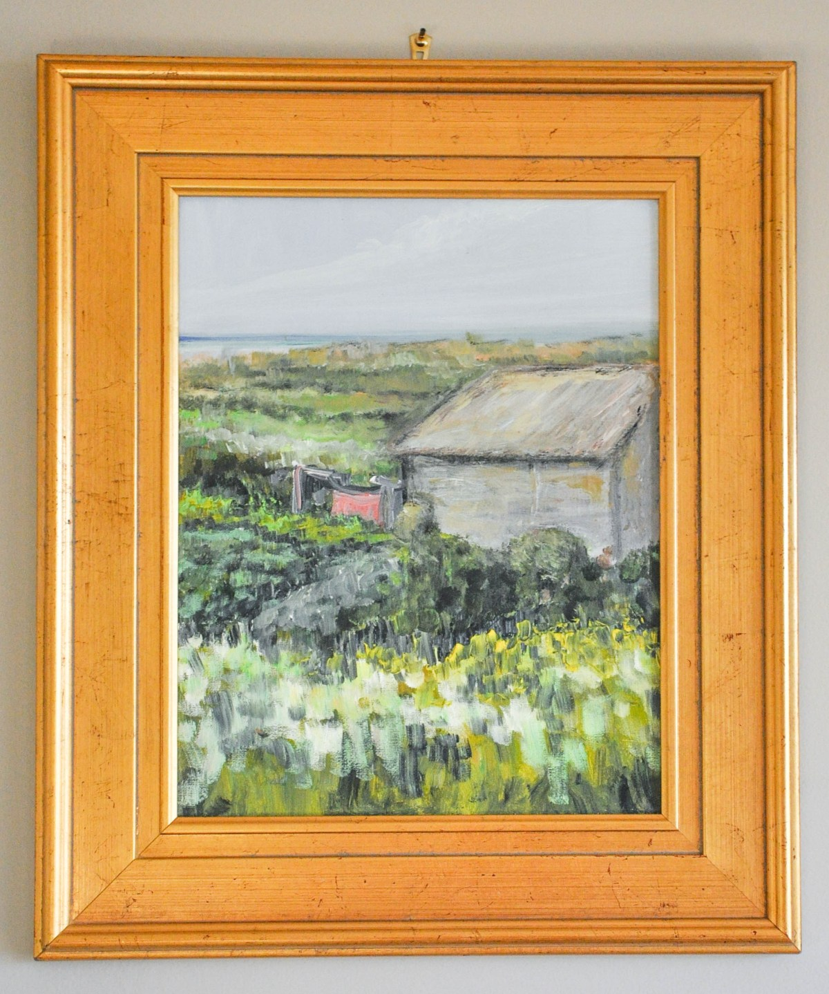 An artwork hanging mistake is highlighted by the nail and hook which are clearly visible above the warm gold frame surrounding a small painting of verdant coastal landscape.