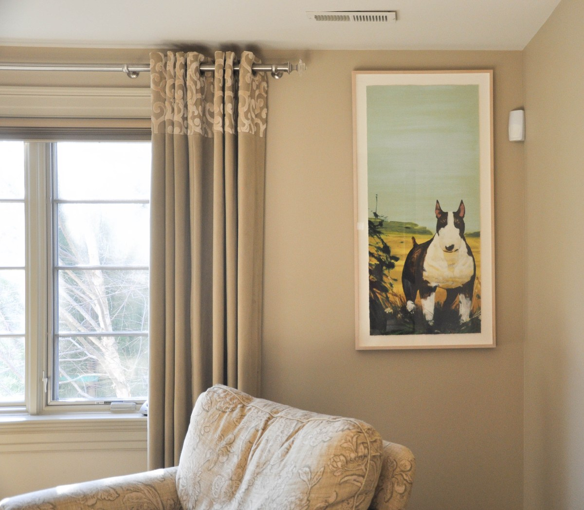 An artwork hanging mistake is highlighted by a large framed art print of a black and white terrier dog that is displayed too high and off-center.