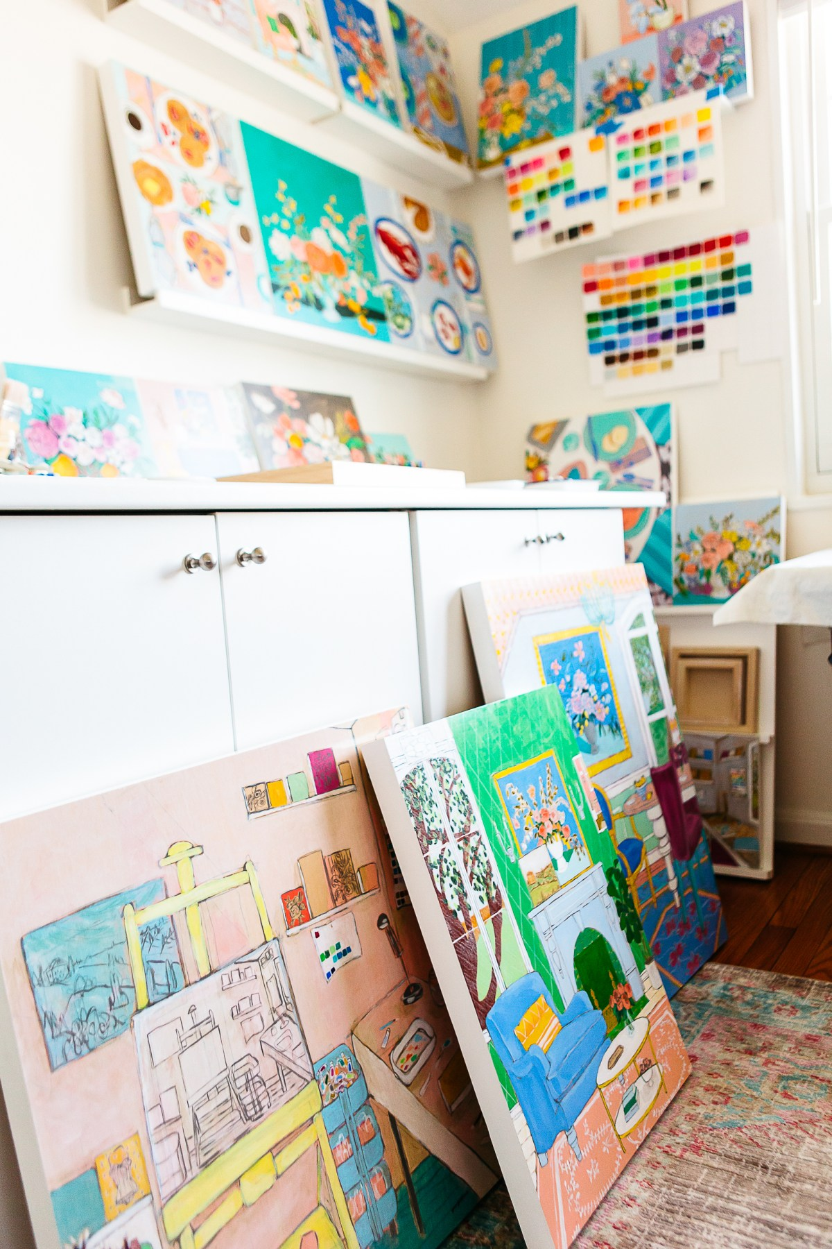 Inside the artist's studio, works by Jennifer Allevato lean against a cabinet and are displayed on shelves on the wall above.