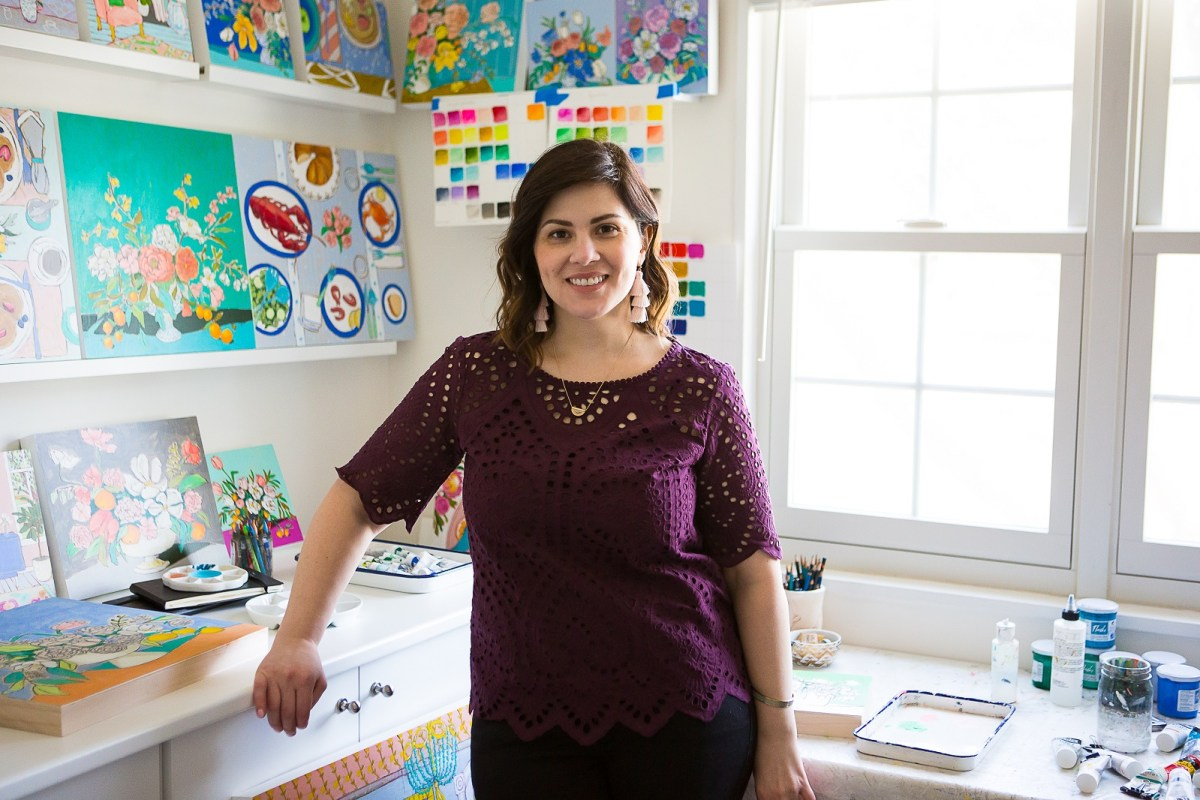 The artist Jennifer Allevato smiles for the camera while standing in her bright and cheery art studio.