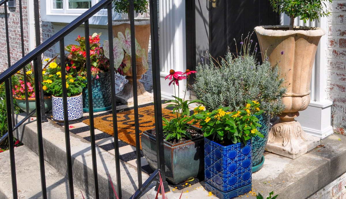 Colorful planter pots filled with summertime flowers are nestled together in two groupings on either side of a front entry's doormat.