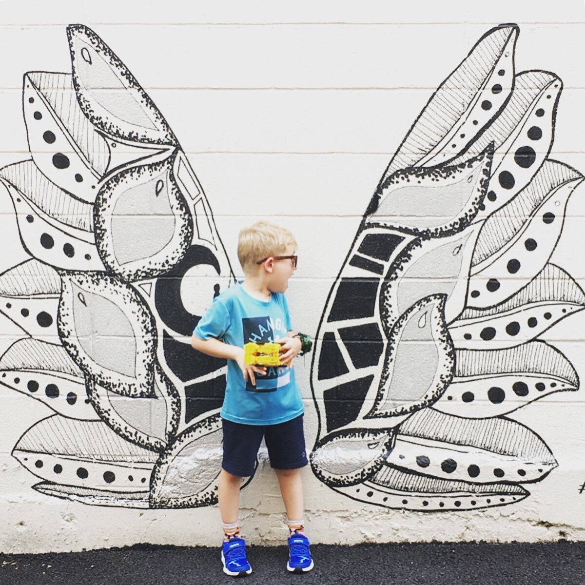 A young boy poses if front of a DC area mural depicting a pair of intricately painted angel's wings.