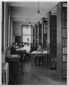 A black and white photo showing students in suits studying and bookshleves