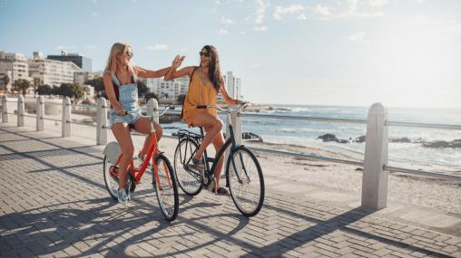 Beste Freunde am Strand auf dem Fahrrad. Behandele dich wie deine beste Freundin um deinen Traummann zu manifestieren