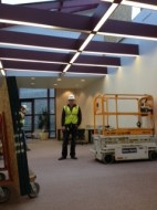 Construction working installing a temporary ceiling above the DAAP Library reading room.