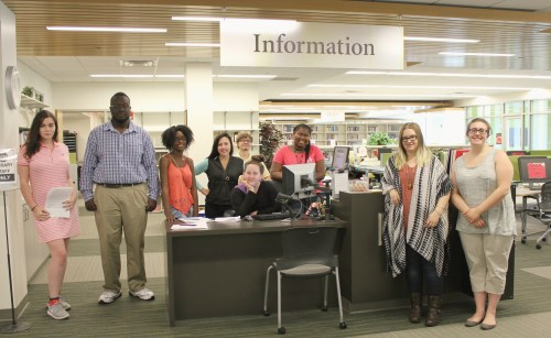 Group of library student assistants standing at the information desk.