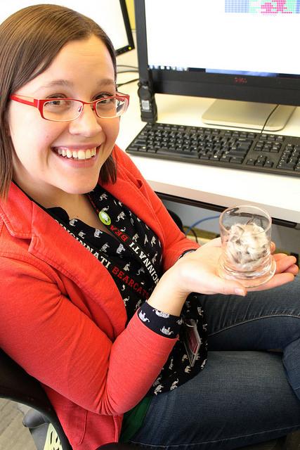 Elizabeth holding a jar of feathers.