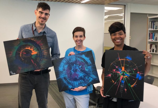 Christian Boyles, Lauren Wahman, and Michelle McKinney holding their spinart