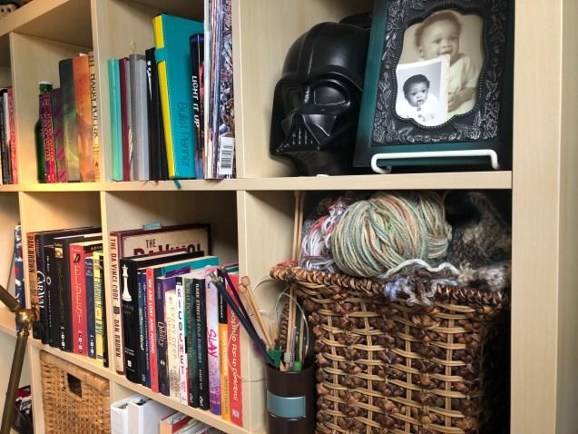 Yarn and knitting needles on bookshelf.