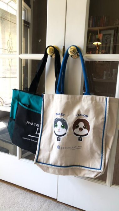 two tote bags hanging from doorknob
