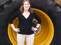 Photo of Lydia Howes at the Farm Progress Show standing in front of a tire that is taller than she is.