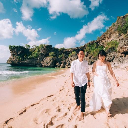 バリ島のビーチを歩く新郎新婦