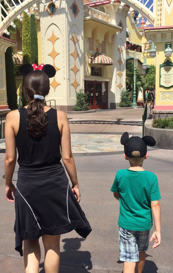 Young woman and little boy in Mickey ears walking at Disneyland
