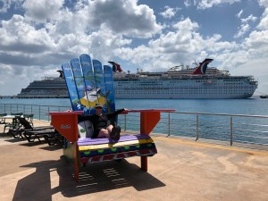 Libby sitting on a big chair in front of a cruise ship in Cozumel