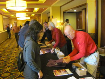 Attendees pick up their materials at the registration desk