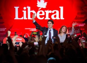 Justin Trudeau, Canada's prime minister-elect and leader of the Liberal Party of Canada, and his wife Sophie Gregoire-Trudeau wave to supporters on election night in Montreal, Quebec, Canada, on Tuesday, Oct. 20, 2015. Trudeau's Liberal Party swept into office with a surprise majority, ousting Prime Minister Stephen Harper and capping the biggest comeback election victory in Canadian history. Photographer: Kevin Van Paassen/Bloomerg