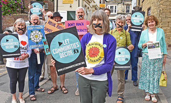 Eight elderly activists hold anti-fracking signs