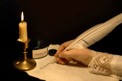 hand writing a letter to editor with a goose feather