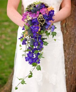 weddings: bride in white dress with long blue bouquet