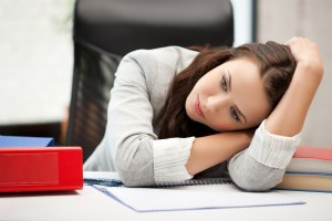bored woman resting head on desk