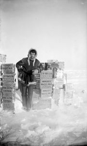 Explorer Ernest de Koven Leffingwell poses with cases of Horlick's Malted Milk on Flaxman Island, Alaska, circa 1910