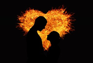silhouette of man and woman with fiery heart