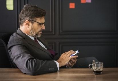 Un patron d'entreprise consulte son portable à sa pause café