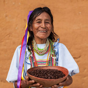 A laughing old Peruvian woman wearing traditional Peruvian clothes and holding a bowl of coffee beans