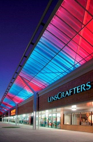 Picture of a colorfully lighted shopping center façade at night with LensCrafters