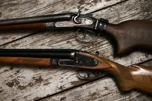 two wooden rifles on a wood plank background