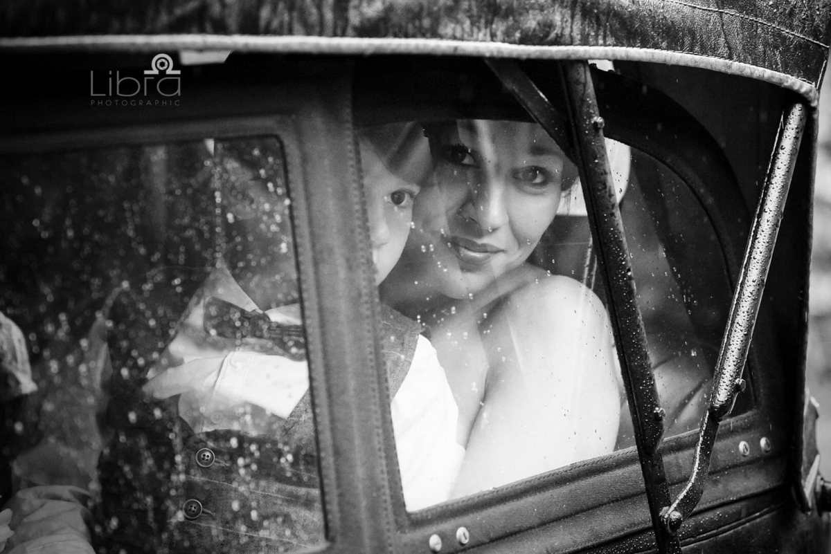 Bride looks out of her wedding car in the rain before the ceremony