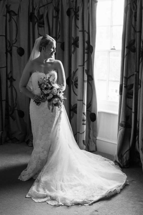 Bride stands by the window at the King John inn - Wiltshire wedding
