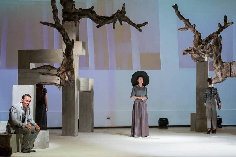 A színpadot egy betontömbökből kitörő, már kiszáradt vagy épp téli álmát alvó, lomb nélküli fa uralja.