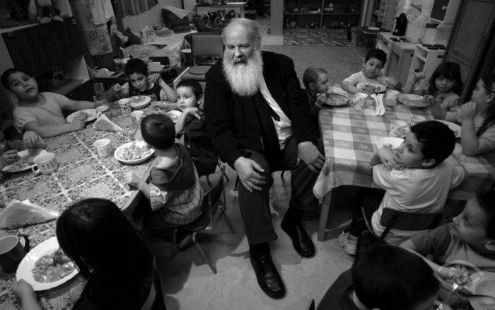 Iványi Gábor lelkész étkező gyermekek között a Magyarországi Evangélikus Testvérközösség óvodájában, 2009-ben (forrás: sajtofoto.hu)