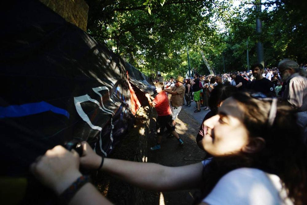 A Liget Budapest projekt ellen tiltakozók rángatják a bontás alatt álló Hungexpo irodaházak kerítésének borítását 2016. július 6-án. MTI Fotó: Balogh Zoltán