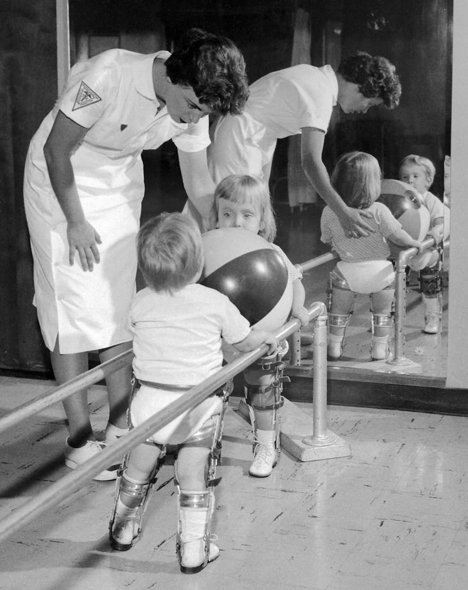 Fizikoterapeuta segít két paralízises kisgyereknek, hogy a korlátba kapaszkodva tartsák magukat. Mindkettőn lábmerevítő van. 1963, Charles Farmer, AVS tray #129, B 54497